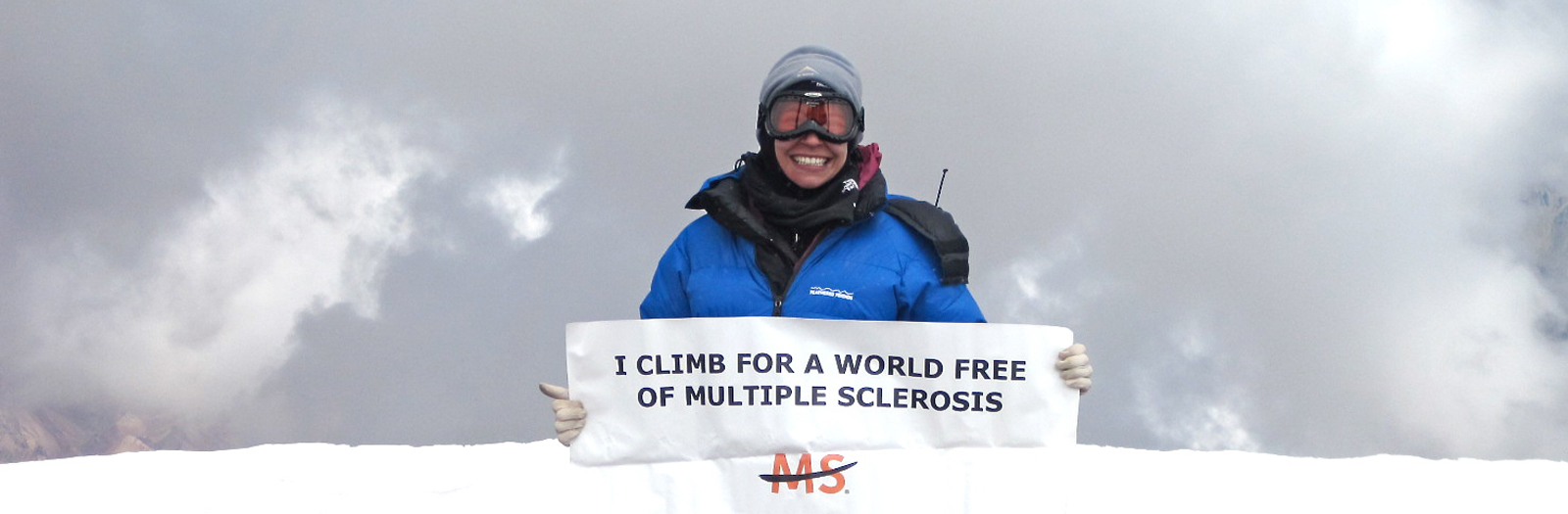 woman climbing mountain and holding sign