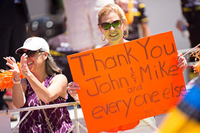 Supporter hold sign that reads Thank You John and Mike and Everyone Else